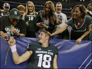 Michigan State's Connor Cook celebrates with fans following the Big Ten Conference championship win.