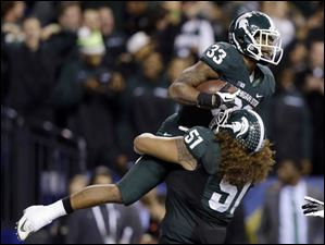 Michigan State's Jeremy Langford (33) celebrates with Fou Fonoti (51) after Langford ran 26-yards for a touchdown during the fourth quarter.