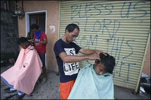 Typhoon survivors get a haircut along the streets for $1 in Tacloban, central Philippines on Sunday.