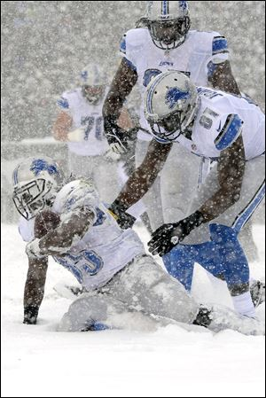 Detroit Lions' Joique Bell, left, gets up with the help of Brandon Pettigrew, center, and Calvin Johnson after scoring a touchdown during the first half.