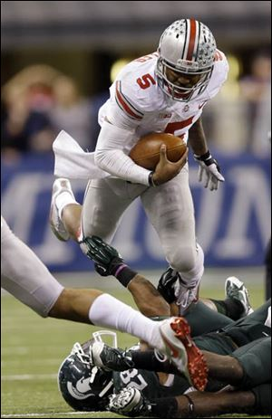 Ohio State's Braxton Miller (5) is tackled by Michigan State's Denicos Allen.