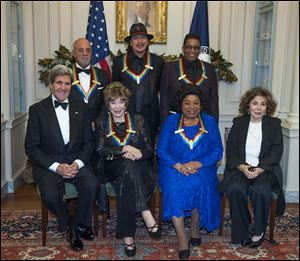 Secretary of State John Kerry, with the 2013 Kennedy Center honorees, from left, seated Shirley MacLain, and Martina Arroyo, along with Teresa Heinz Kerry. Standing are Billy Joel, Carlos Santana, and Herbie Hancock.