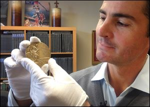 Dan Imler of SCP Auctions shows Jessie Owens gold medal from the 1936 Olympics at the SCP Auctions in Laguna Nigel, Calif.