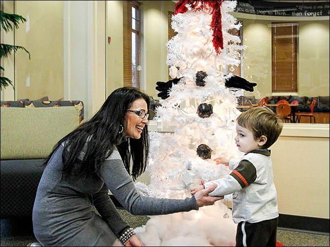 9n2snowtree-8 Shelley Skiver shows her grandson Collin Clark one of the decorated Christmas trees inside the Bedford Branch Library in Temperance. Seventeen trees with different themes are on display.