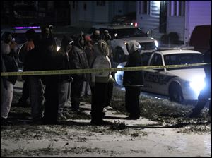Bystanders, many of them reportedly family members of the slain men, watch as police investigate 2 deaths at a home on E. Pearl St. in Toledo, Ohio.