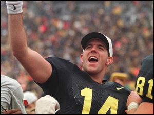 Michigan quarterback Brian Griese (14), acknowledges the crowd with a rose in his hand after he led the Wolverines to a 20-14 win over Ohio State at Michigan Stadium in Ann Arbor, Saturday, Nov. 22, 1997.