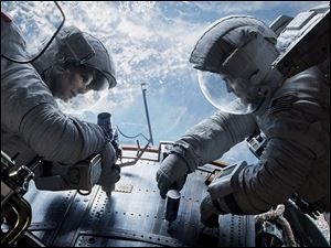 Sandra Bullock, left, as Dr. Ryan Stone and George Clooney as Matt Kowalsky in 'Gravity.' The space odyssey and the futuristic romance 'Her' tied for best picture from the Los Angeles Film Critics Association. The L.A. critics announced their picks Sunday.