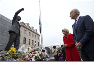 Vice President Joe Biden, right, and wife Jill Biden, pay their respects to former South African President Nelson Mandela outside the South African embassy in Washington, today, after signing a condolence book inside.