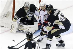 Columbus Blue Jackets center Boone Jenner, center, can't get a shot off between Pittsburgh Penguins goalie Marc-Andre Fleury (29) and Pittsburgh Penguins' Simon Despres (47) in the first period.