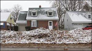 Leaves are piled along the curb in front of some of the homes on Beverly Drive in South Toledo.