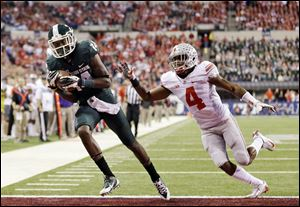 Michigan State's Tony Lippett, left, makes a 33-yard touchdown reception against Ohio State's C.J. Barnett (4) during the first half of a Big Ten Conference championship NCAA college football game Saturday, Dec. 7, 2013.