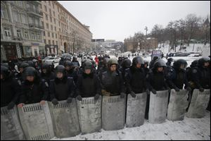 Ukrainian riot police block the road next to Pro-European Union activists gathered on the Independence Square in Kiev, Ukraine today.