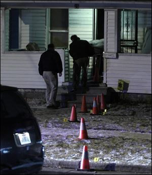 One of two slain men is removed from a home on E. Pearl St. in the Polish Village.