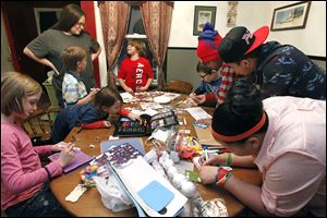 From bottom  left:  Makayla Brighton, 9, Dexter Thomas, 2, Jacob Brighton, 6, Melissa Thomas, standing, Emilee Morales, 8, Derrick Bettinger, 10, Brandon Harris, 12, Alex Risby, 16, and Shai Harris, 14, make cards for the Marines they adopted for the holidays.