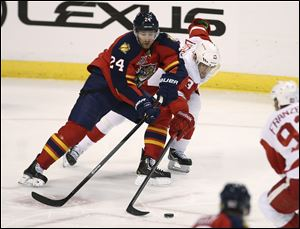 Florida Panthers' Brad Boyes (24) and Detroit Red Wings' Pavel Datsyuk (13) chase the puck during the second period.