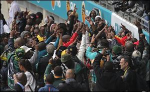 People dance as they arrive for the memorial service for former South African president Nelson Mandela at the FNB Stadium in Soweto, near Johannesburg, South Africa.