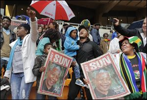 People hold images of  former South African president Nelson Mandela ahead of his memorial service.