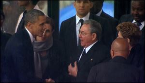 President Obama shakes hands with Cuban President Raul Castro at the FNB Stadium in Soweto, South Africa, in the rain for a memorial service for former South African President Nelson Mandela.