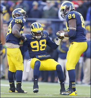 University of Michigan players Fitzgerald Toussaint (28) and A.J. Williams (84) helps quarterback Devin Gardner (98) to his feet. Gardner apparently incurred turf toe during this game Saturday, November 30, against Ohio State.