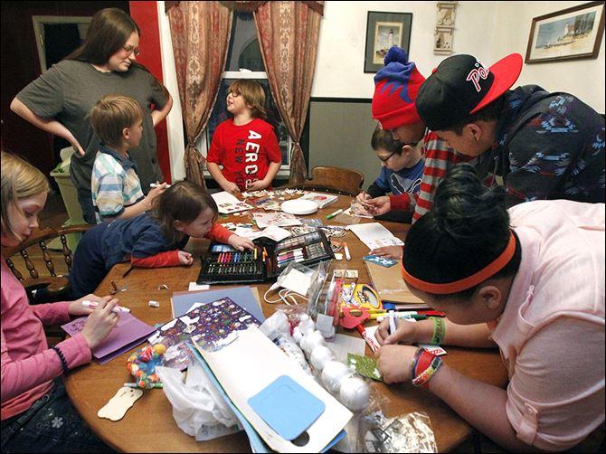 11n4make-1 From bottom  left:  Makayla Brighton, 9, Dexter Thomas, 2, Jacob Brighton, 6, Melissa Thomas, standing, Emilee Morales, 8, Derrick Bettinger, 10, Brandon Harris, 12, Alex Risby, 16, and Shai Harris, 14, make cards for the Marines they adopted for the holidays.