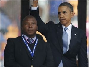 President Obama waves standing next to the sign language interpreter after making his speech at the memorial service for former South African president Nelson Mandela at the FNB Stadium in Soweto near Johannesburg.  South Africa's deaf federation said today that the interpreter on stage for Mandela memorial was a 'fake.'