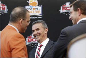 OSU's Urban Meyer, center, and Clemson's Dabo Swinney, right, have a laugh with Eric Poms, the Orange Bowl Committee's CEO.