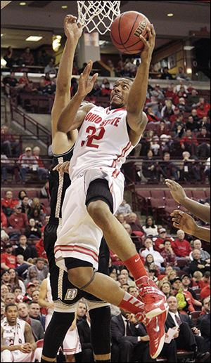 Ohio State's Lenzelle Smith, front, shoots over Bryant's Claybrin McMath during the second half.