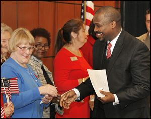 Chris Burkhart of the Fort Industry chapter of the Daughters of the American Revolution congratulates Andrew Mwangi Gitongu, who was among 39 people who became  citizens Thursday.
