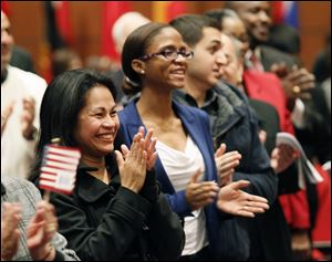 Nancy Padayogdog Hierholzer, left, formerly of the Philippines, and Tracey Annrose Hidalgo, formerly of Trinidad and Tobago applaud Thursday during a naturalization ceremony for 39 new U.S. citizens held at the Main Library downtown.