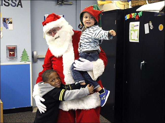 Santa Claus, played by William Smith with the UAW, holds Jett Reynolds, 2, right, and he gets a hug from DeAndre Patterson, 5, left, while visiting the children of Toledo Day Nursery.