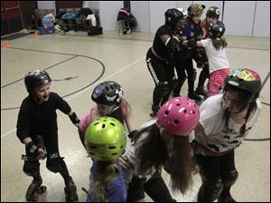 Rose Nye, 10, left, practices her jamming as she attempts to pass through a line of blockers.