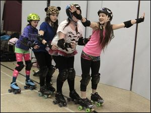 Gillian Watson, 13, right, pulls a line of her teammates during practice with the Frogtown Fallgirls Junior Roller Derby team at Common Space in West Toledo.