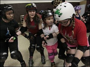 Samarya Jones, 13, left, Elizabeth Porter, 15, center left,  Kyleigh Bialecki, 9, center right, and Jaelyn Prater, 13, right, attempt to block another skater together.