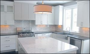 Carrara marble tops the large kitchen island and contrasts with the steel gray countertop.