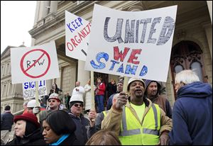 Union workers rally outside the Capitol in Lansing, Mich., in this 2012 file photo.