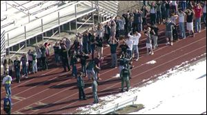 In this still image taken from video provided by Fox 31 Denver,  students gather just outside of Arapahoe High School as police respond to reports of a shooting at the school in Centennial, Colo.