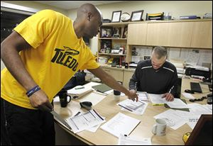 Toledo assistant coach Jason Kemp, left, gives statistics to coach Tod Kowalczyk before the Rockets played Robert Morris. Kowalczyk believes statistical analysis can be beneficial to the team.