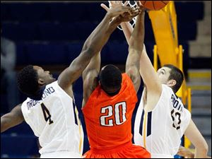 University of Toledo players Justin Drummond (4) and Nathan Boothe (53) defend Sam Houston State player James Thomas during the first half.