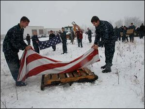U.S. Navy Sea Cadets Joe Hines, of Swanton, left, and Ryan Libstorff, of Bedford, Michigan, place the flag from which the star field had been cut from the stripes on the fire. It is the first to be incinerated.