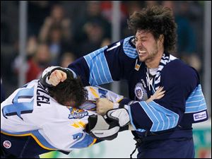 Toledo Walleye player Richard Nedomiel (24) and Evansville IceMen player Sawyer Hannay (7) fight during the second period.
