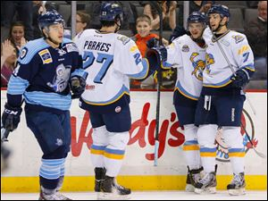 Walleye players Trevor Parkes (27) Martin Frk (19) and Max Nicastro (7) celebrate Frk's goal against Evansville IceMen during the first period.