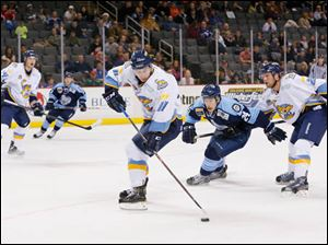 Walleye player Scott Arnold (11) picks up a loose puck against the Evansville IceMen during the second period.