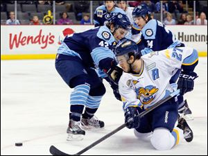 Toledo Walleye player Trevor Parkes (27) tries to shoot the puck around Evansville IceMen player Jacob Johnston (42) during the first period.