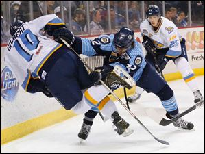 Walleye player David Gilbert (10) is hit by IceMen player Jacob Johnston (42) during the first period.