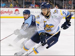 Toledo Walleye player Max Nicastro (7) steals the puck from Evansville IceMen player Daultan Leveille (19) during the second period.