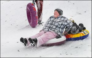 Toledoan Amanda Williams and her son Elijah, 6, 'tube' down the Wagener Sledding Hill at Side Cut Metropark in Maumee. Saturday's snowfall reached 8 inches in Toledo and surrounding areas.