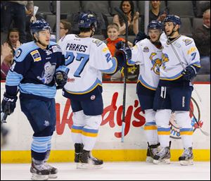 Toledo Walleye players Trevor Parkes (27) Martin Frk (19) and Max Nicastro (7) celebrate Frk's goal against Evansville IceMen during the first period.