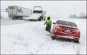 A wrecker driver removes a car that slid off the Ohio Turnpike westbound near the Maumee exit.