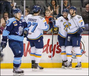 The Walleye's Trevor Parkes (27) Martin Frk (19) and Max Nicastro (7) celebrate Frk's goal against Evansville.