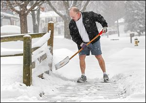 Ken Dreeze shovels his sidewalk in Maumee — in shorts. After all, winter is still a week away.  Temperatures though will remain in the mid-20s today, and 30 mph winds are expected.
